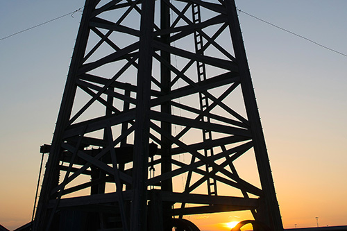 a drill tower with the sunrise behind it