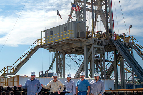 five workers with helmets and security glasses standing up in front a tower