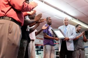 Commissioner Bill Fennoy presents Ray Whitfield with a proclamation honoring the Augusta Boxing Club's 40th anniversary.