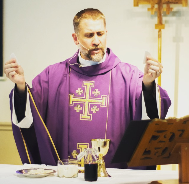 Father Chris Richardson at the altar with the Host, Chalice, and Liturgy for Eucharist.