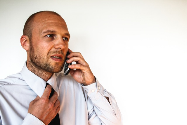man on phone pulling at his tie