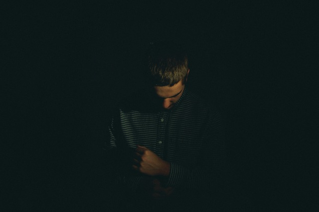 man with head down in dark place