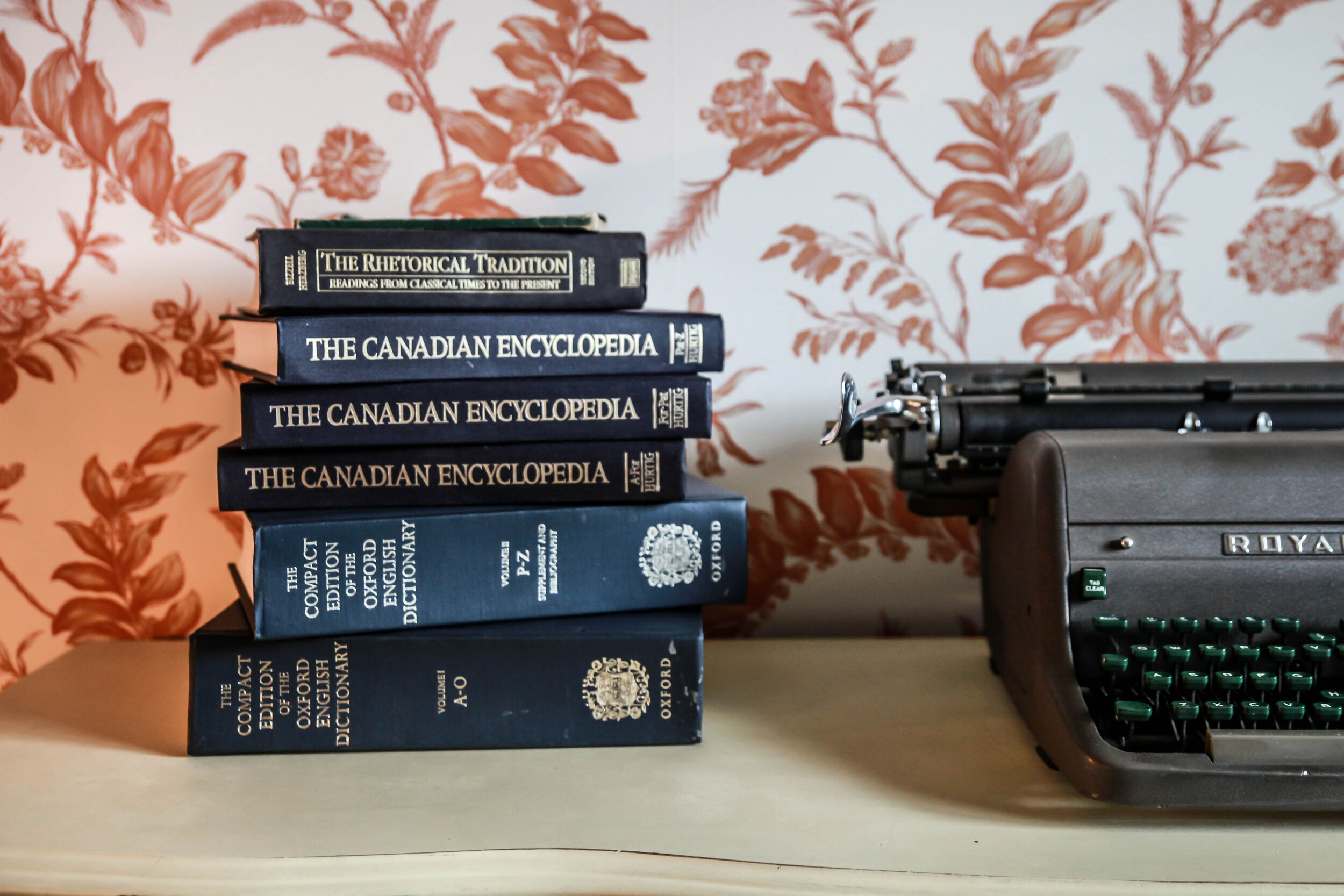 Stack of Oxford English Dictionaries and Canadian Encyclopedias beside a typerwriter.