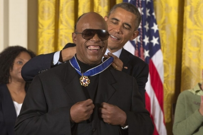 Photo by: Jacquelyn Martin Musician Stevie Wonder celebrates as President Barack Obama awards him the Presidential Medal of Freedom, Monday, Nov. 24, 2014, during a ceremony in the East Room of the White House in Washington. President Obama is presenting the nation's highest civilian honor to 19 artists, activists, public servants and others. (AP Photo/Jacquelyn Martin)