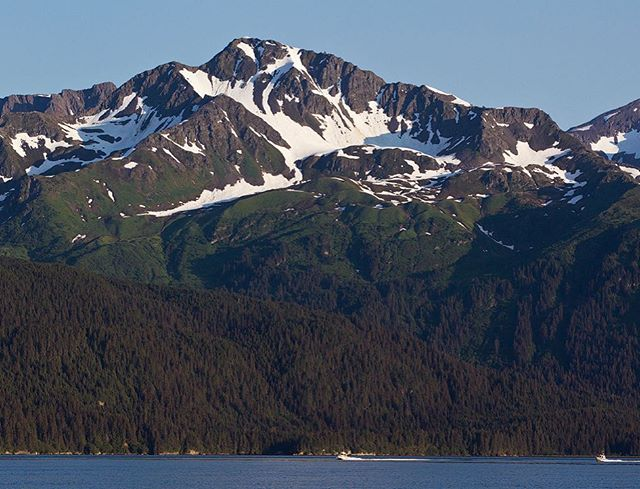 Fishing boats dwarfed by rugged peaks of the Alaskan mountains