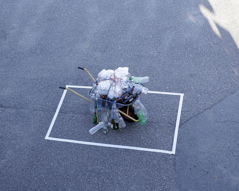 """Bottle sculpture in a wheelbarrow"" by Bärbel Praun."