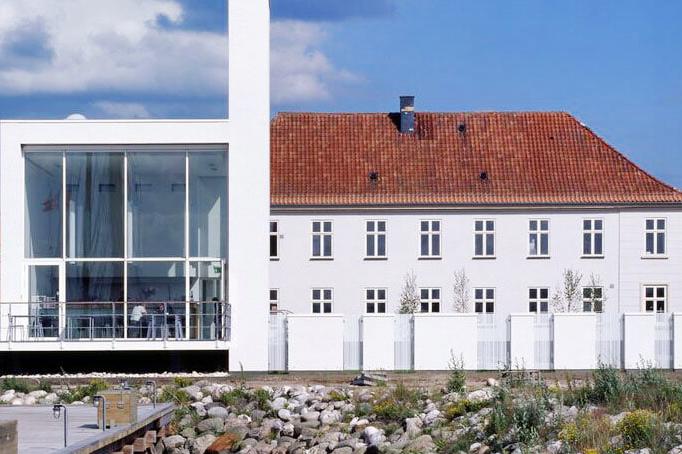 """Glasmuseet Ebeltoft   """"Glasmuseet Ebeltoft blev oprettet i 1985 i den tidligere Toldbod i den mere end 700 år gamle købstadsby Ebeltoft, som ligger ved Ebeltoft Vig. Museet blev til på initiativ af den danske glaskunstner Finn Lynggaard og realiseret i tæt samarbejde med tidligere direktør for Kvadrat, Erling Rasmussen og statsautoriseret revisor, Bent Fredberg.""""   Adresse:  Strandvejen 8, 8400 Ebeltoft.  Links:   Glasmuseet.dk   Foto:  Glasmuseet Ebeltoft."""