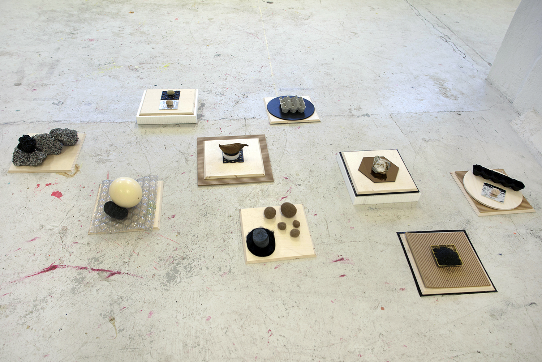 Mette Borup Kristensen, Uden titel (træ, sten, æggebakker, spejl, plastik, bobleplast, flamingo, strudseæg, glimmer, tekstil, sort sand, asfalt, organisk materiale).