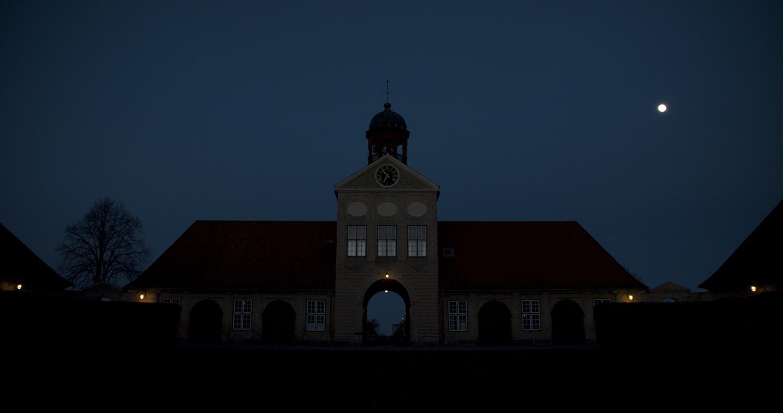 EQUILIBRIUM STATE, 2019. En hovedakse fra Augustenborg Slots midte går gennem Portbygningen og munder ud i Slotsalléen med to rækker af bevaringsværdige villaer. I klokketårnet, Hertugbyen Augustenborgs logo, hænger slotskirkens klokkespil i nogen afstand fra selve kirken. Normalt hører man kirkeklokker fra afstand, når de ringer ind til samling, mens tårnet er vejviser. Det er derfor særligt, at man kan stå i porten under klokkerne og høre dem ringe - uden at man kan se dem. Lars Lundehave Hansen har ønsket at udviske modsætningen mellem rummets og klokkernes position. I selve porten er to døre omdannet til højttalere, som spiller en symfoni af klokkespil. På vej gennem rummet hører passerende en lav ringen, men stiller de sig et øjeblik og lytter, bliver de hurtigt draget ind i et meditativt rum med et uendeligt klokkespil. Lars Lundehave Hansen har også lyssat klokkerne, så de synes i dagslys og lyser op om aftenen. Med et næsten usynligt indgreb har han omtolket klokkernes funktion til en kunstnerisk oplevelse og givet dem en ny betydning i slottets rum. (Video still: GotFat Productions).