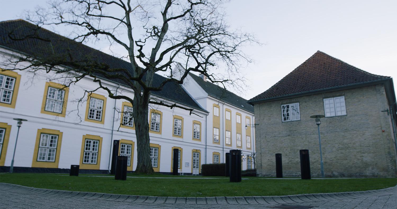 DIM REALM, 2019. Foran Slotskirken er en lille, firkantet og kortklippet græsplæne med et stort træ. Et rum der blev til overs og siden rammet ind af asfalt og pullerter, pyntet med lygtepæle i galvaniseret stål og gennemskåret af en sti med betonfliser. Med sit værk DIM REALM har Lars Lundehave Hansen nu ophøjet et før overflødigt og effektivt rum til et egentligt sted, et centrum. Værket bringer kirkeorglets lyd udenfor i et ceremonielt rum. De otte stålsøjler danner et akustisk og visuelt rum og giver fysisk form til kompositionen af et 8-kanalers lydværk. Værkets grundelement er en blæsende tone, hvorfra akkorder ganske langsomt vinder frem for kort efter at forsvinde igen, og værket vender tilbage til sin grundtilstand. En cyklus, der indtræder flere gange i løbet af en dag. Stien bringer et intetanende publikum igennem værket, når de går til og fra parkeringspladsen.  Forbipasserende kan fornemme lydene svagt. Står de stille for en tid vil de svømme ind i lydbilleder, der aldrig gentager sig selv. (Video still: GotFat Productions).