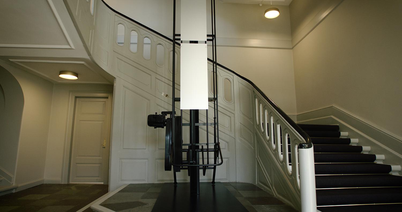STACKING FREQUENCIES, 2019. I Nordfløjens indgangsparti, Landbrugsstyrelsens officielle hovedindgang med mødecenter, spænder en 10 meter høj balletransportør rummet ud. Tidligere flyttede skulpturen halmballer, i dag flytter den sommerlandskabets lyde fra grundetagen og op til øverste repos. Trappen snor sig omkring skulpturen, indrammer den, og alene i kraft af sit udtryk, position og højde frembringer skulpturens trapperummets dimensioner, funktion og rumlighed. Syv aluminiumsplader fungerer som resonansplader for en 7-kanalers lydinstallation. Værket afspiller en række tyste kompositioner, der minder om vindens susen i højspændingskabler eller melodien et søvnigt vindspil. Lyde, man forbinder med en stille sommerdag på landet. Lyde, der indlejrer sig umærkeligt i rummets naturlige akustiske ambiens. Lyde, man lige akkurat hører, når man passerer. Det er nemlig ikke et værk, man skal høre. Man skal opdage, at man hører det. Opdager man lydene, oplever man, hvordan de flytter sig rundt i rummet, tager til og stilner af, og skaber et stilfærdigt og intimt rum. (Video still: GotFat Productions).