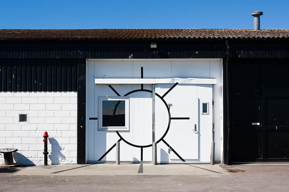 """Sol   """"Sol er et kunstnerdrevet udstillingssted beliggende på havnen i Nexø på Bornholm. Vi organiserer udstillinger med lokale og internationale kunstnere, som tager kritisk stilling til deres materiale såvel som deres omgivelser. Gennem længerevarende samarbejder med de inviterede kunstnere ønsker vi at udfordre etablerede udstillingsformater og samtidig styrke interessen for samtidskunst i vores lokale miljø.  Udstillingsprogrammet for 2019 er kurateret af Sofie Amalie Andersen.""""   Adresse:  Sdr. Hammer 14, 3730 Nexø.  Links:   Solnexoe.com   Foto:  Sol, 2019."""