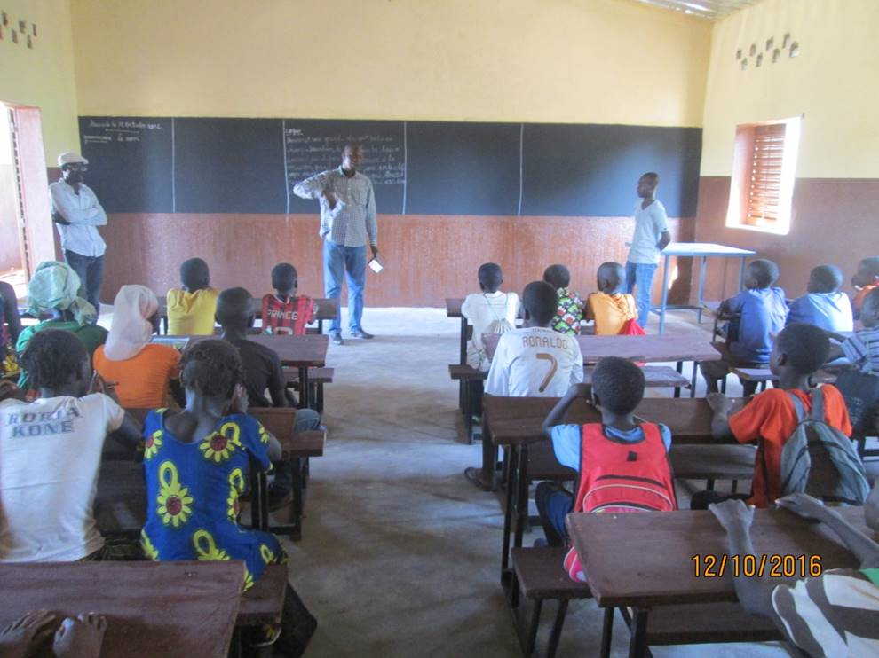 Children in Fadioubougou's new 7th grade classroom are greeted by Mali Rising's Field Director, Alou Doumbia.