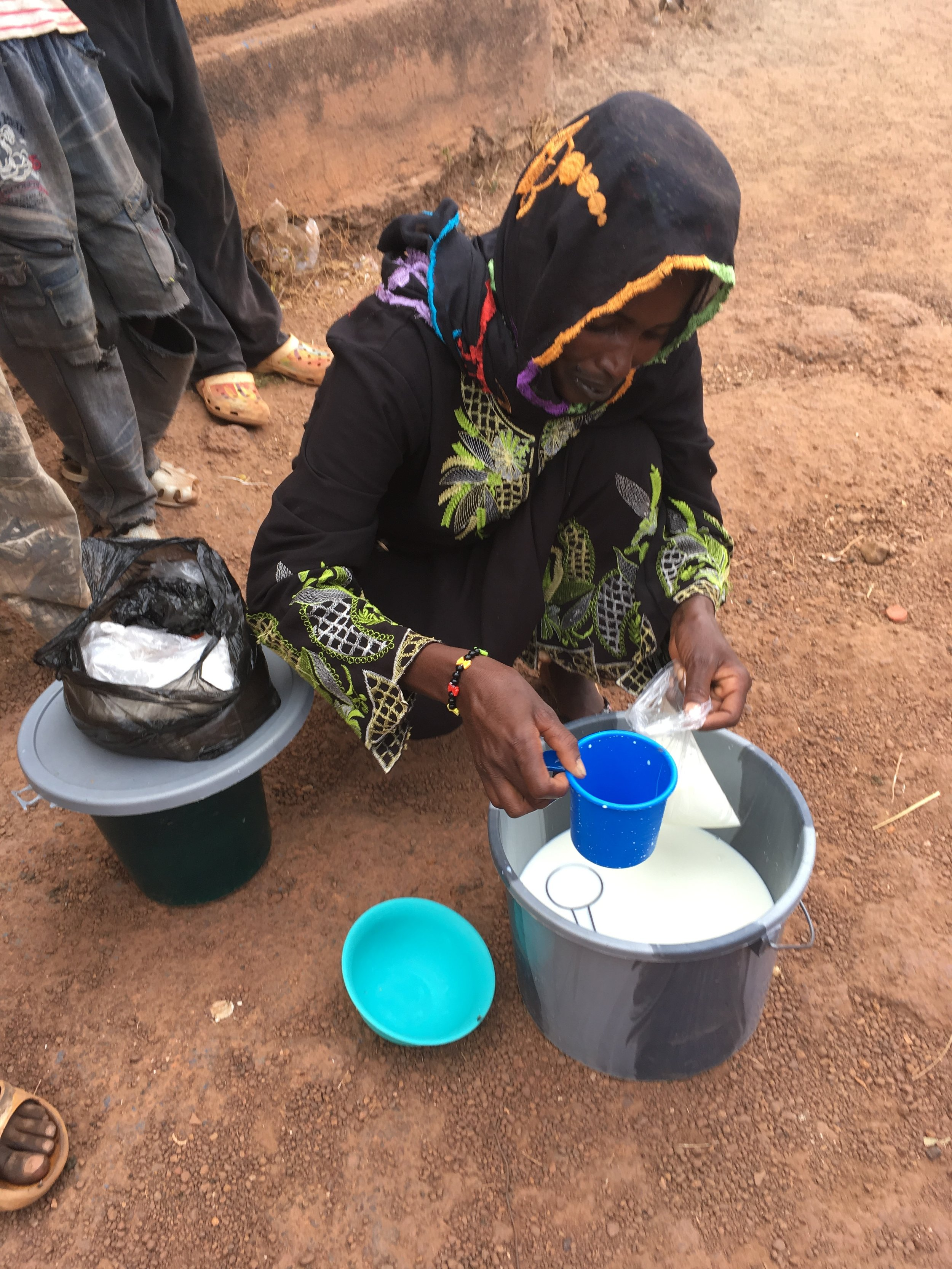Buying milk at the market in Mali.