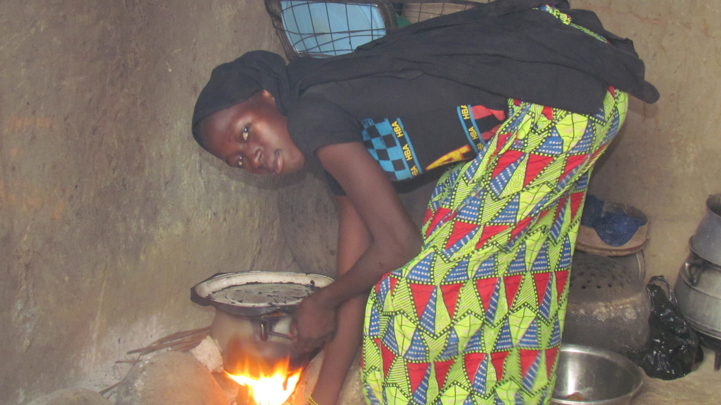 Household chores for girls like Adiaratou are a constant pressure. Here, she cooks a meal for the family.