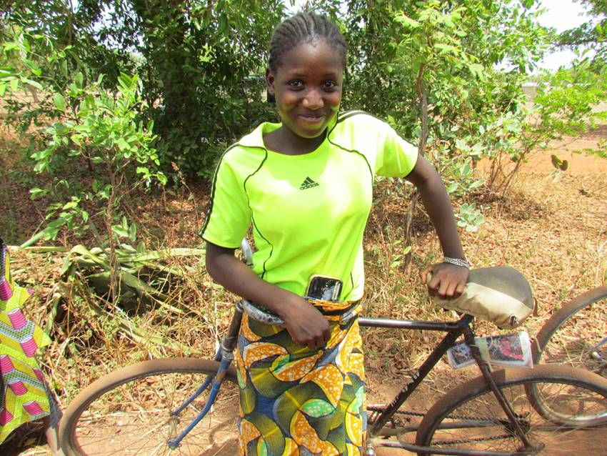 A bike is a hand tool for covering the long, dusty road to school for girls like Alima, who face long, hot trips on dusty roads.