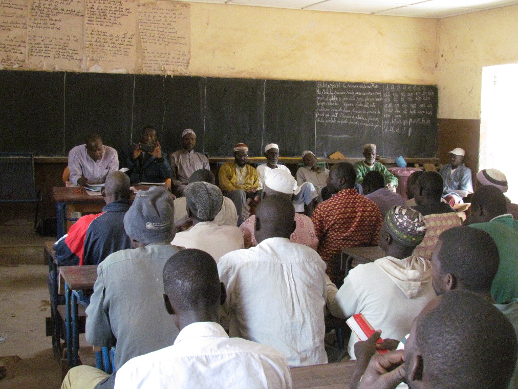 Field Director Alou meets with village members to discuss their interest in a school for their children.