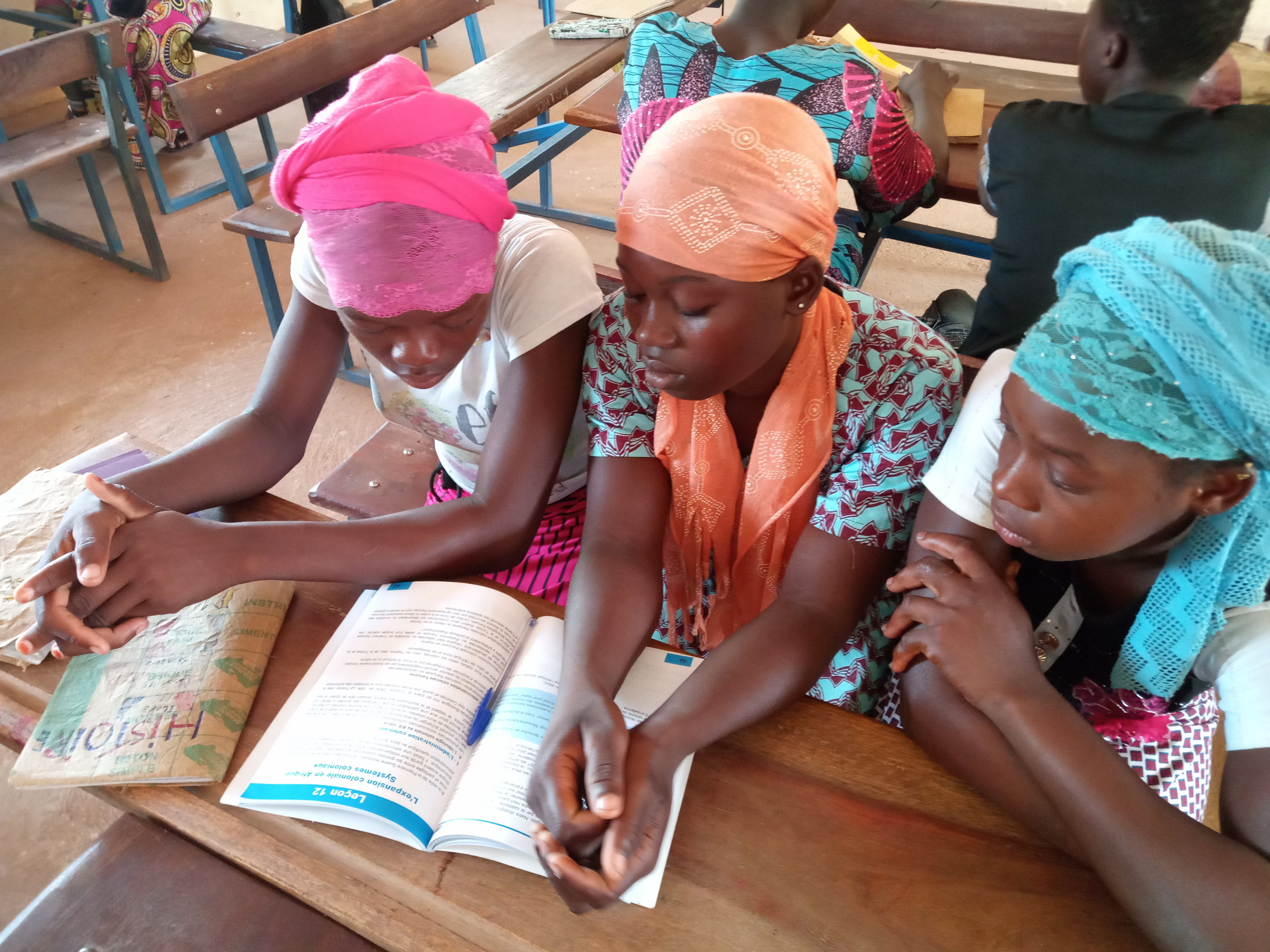 Three girls work together on a lesson in Souleyman's class. Encouraging teachers to use more engaging, active learning strategies is crucial in Mali, .