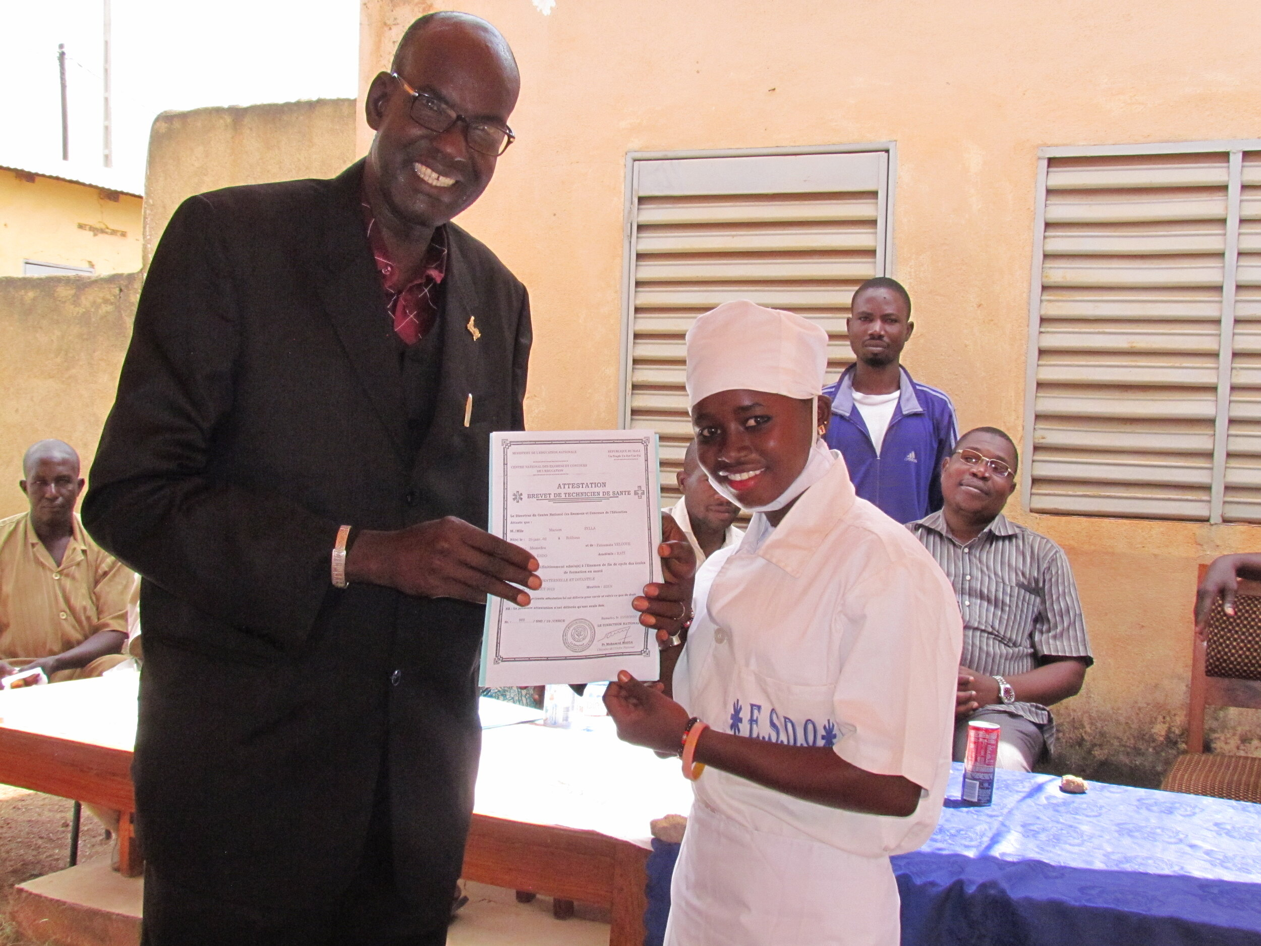 Mariam smiles happily as she graduates from nursing school.
