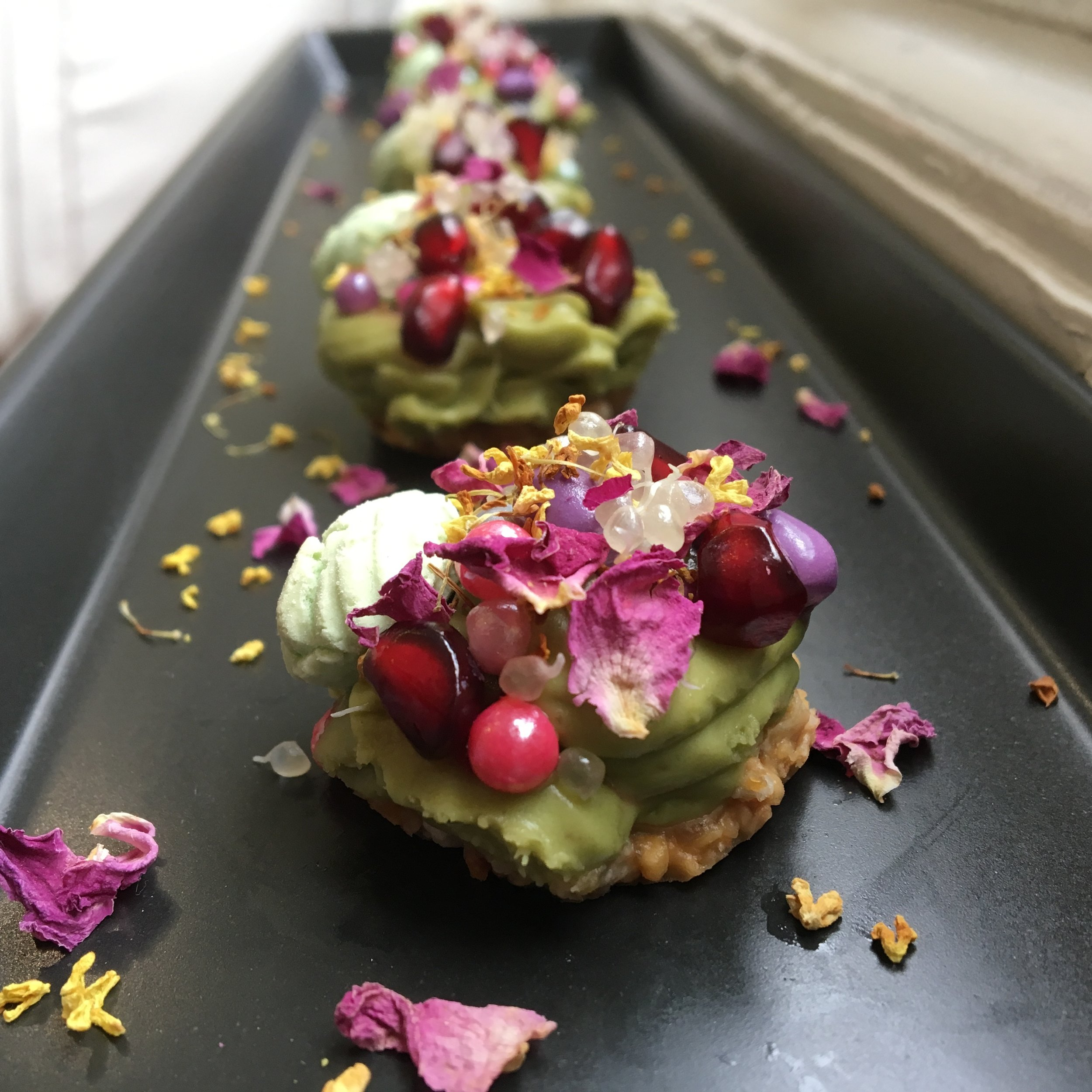 Dessert Canapé      Avo Crown $6.5      Raw avocado cheese, rainbow pearls, finger lime, tic tac, pomegranate, dried rose petal and osmanthus flowers on citrus nutty cookies.