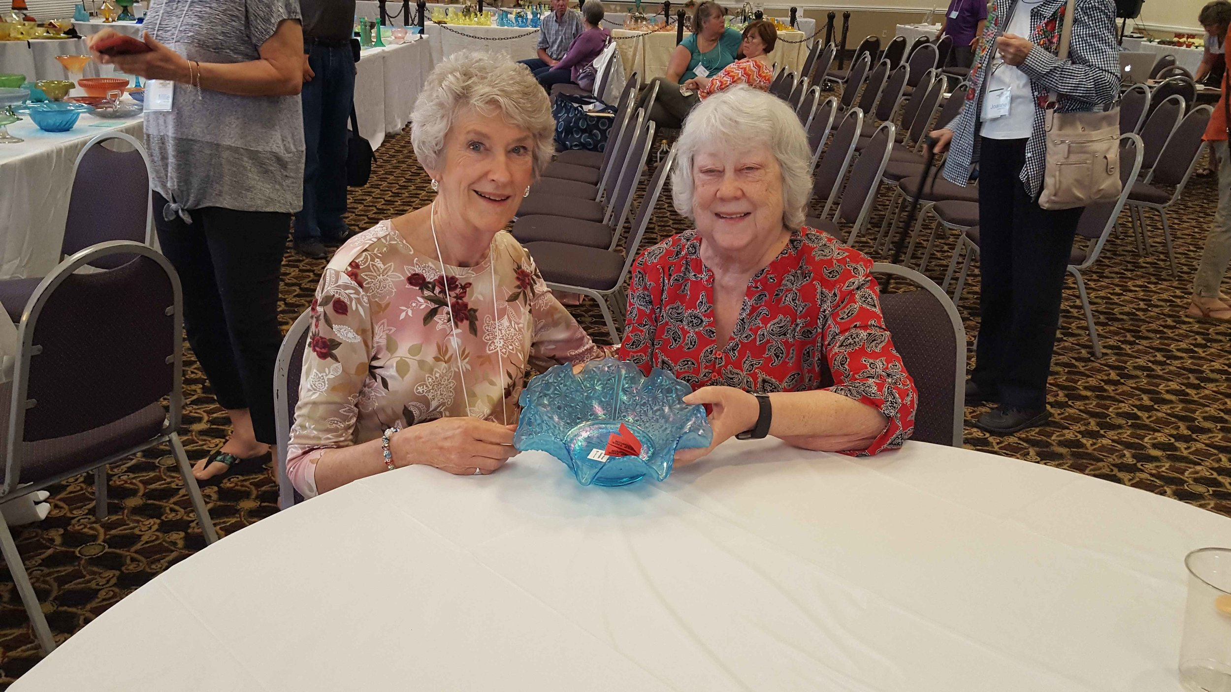 "Helen Jones (right) receiving a gift of a late period Fenton Celeste Blue Daisy & Button ""sample"" bowl from Mary Elda Arrington on behalf of the Museum of American Glass."