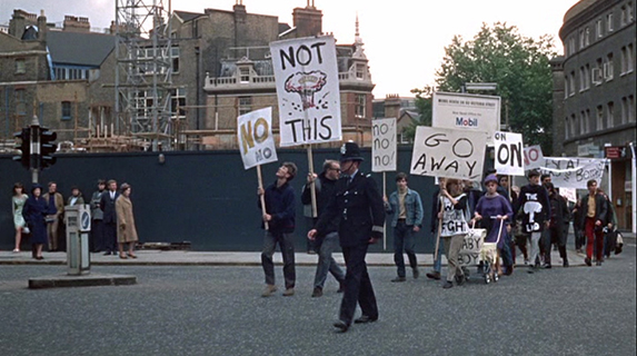 """Blow-Up  The protest march near the beginning of the film that is juxtaposed with the mimes and Thomas driving his Rolls Royce through London - he accepts the offering of the """"no"""" sign as a token but immediately looses it."""