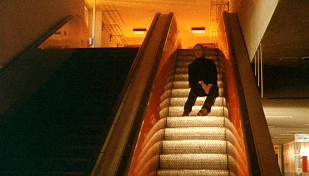 Toby Dammit  Taking the escalator up but facing backwards - surrounded by people but suddenly alone.