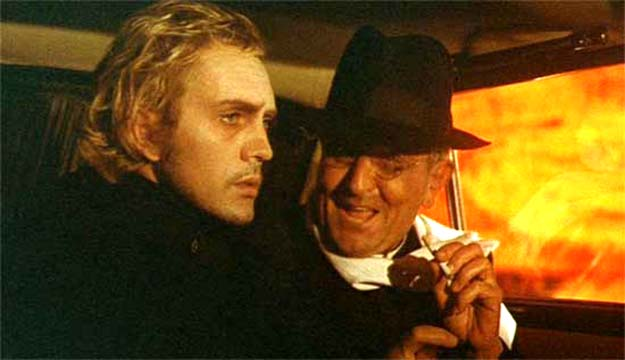 """Toby Dammit  Toby is instructed by the priest/producer that he is to make a """"Catholic Western."""" Note the cigarette and the openly sybaritic attitude by the priest compared to Toby's ethereal, romantic, ascetic disengagement. Despite their physical proximity the two men occupy radically different psychological spaces."""