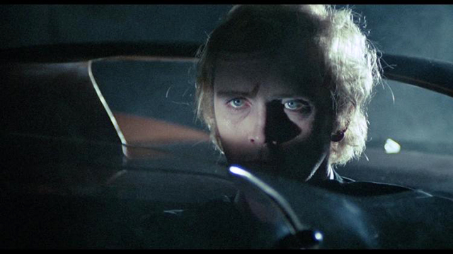 Toby Dammit  Great lighting focuses on the eyes as a subtle triangle of orange - the color most prominent from the airport scene - points to the face of Toby looking doomed while pinned inside his car by the narrow windshield in the front and the roll bar in the back.