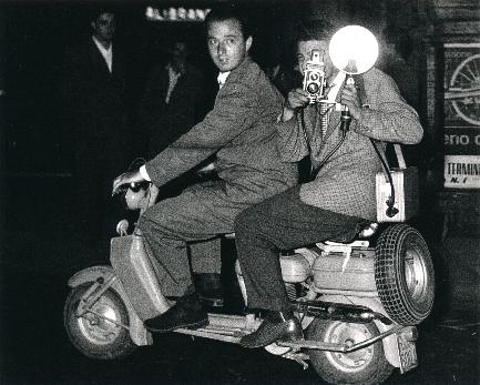 Unknown Photographer,  Tazzio Secchiaroli.  Secchiaroli is at the throttle of a Lambretta with Luciano Mellace behind him with a Rolleicord camera with flash. 1952