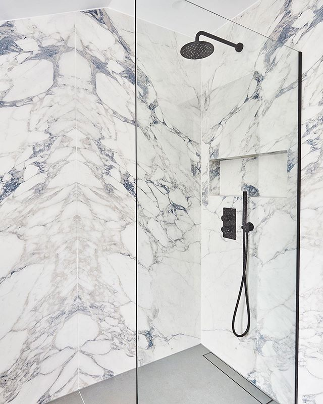 The guest shower...Can I come and stay please? We installed bookmatched 3m faux Arabescato Stuario tiles. Swipe to see the before image! #fauxmarble #interiordesign #design #huxleyhome #lussostone #bathroomdesign Abbeville road, SW4
