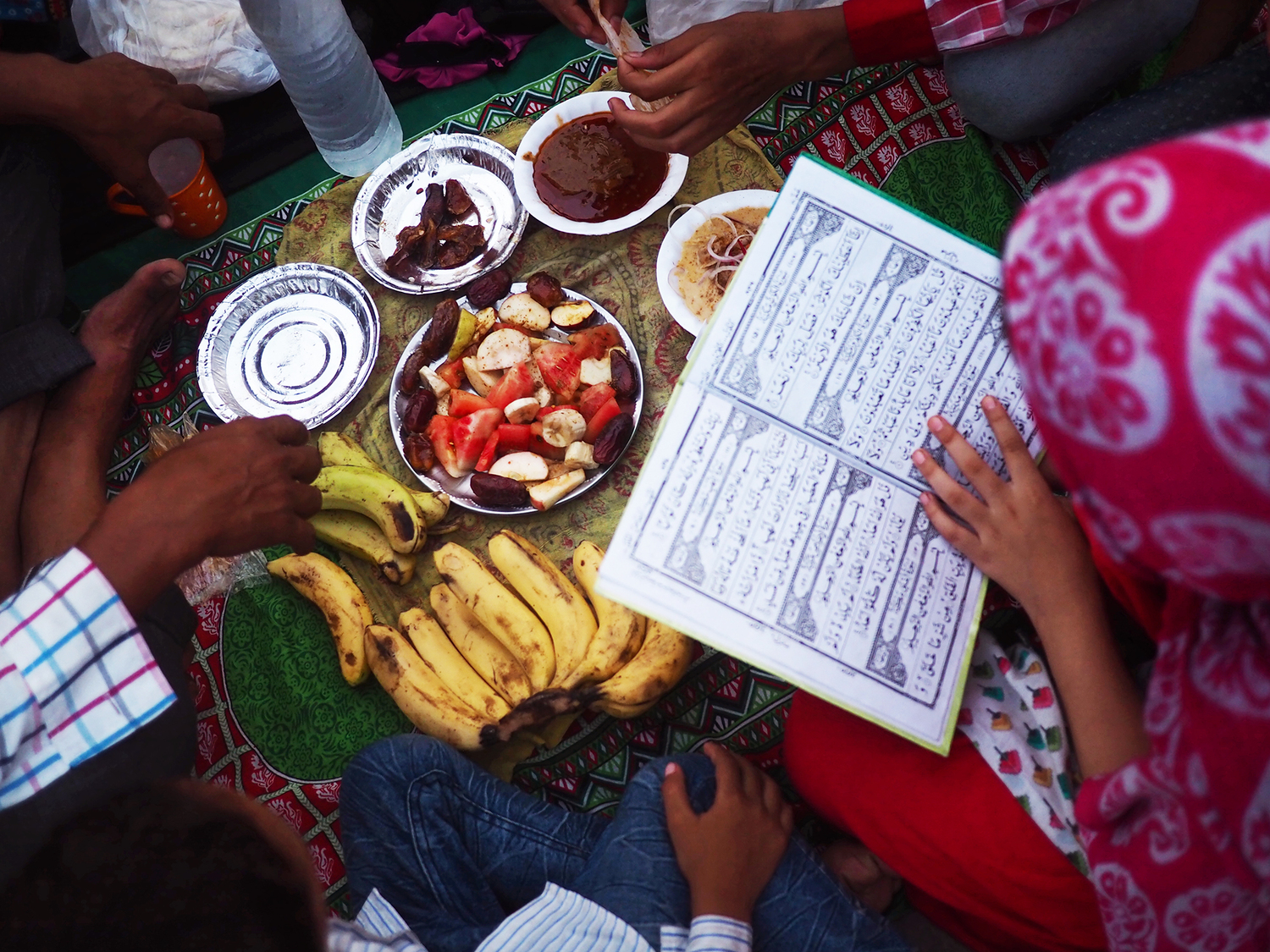 A young girl studies the Quran as her family prepares for the breaking of fast.