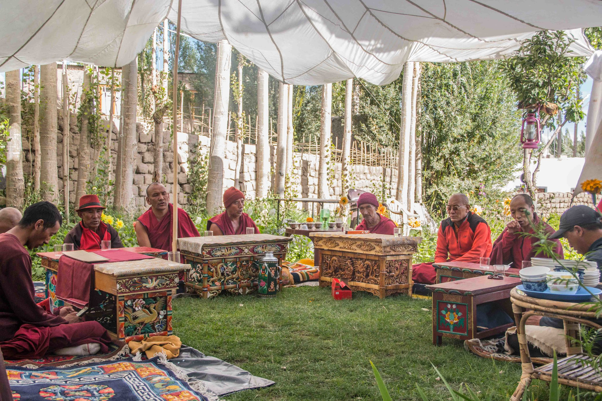 Leh,  Pankaj Singh . Monks conducting a holy recital take a break at a home. Traditional tables called the Choktse are laid out to serve them butter tea, biscuits and Thukpa.