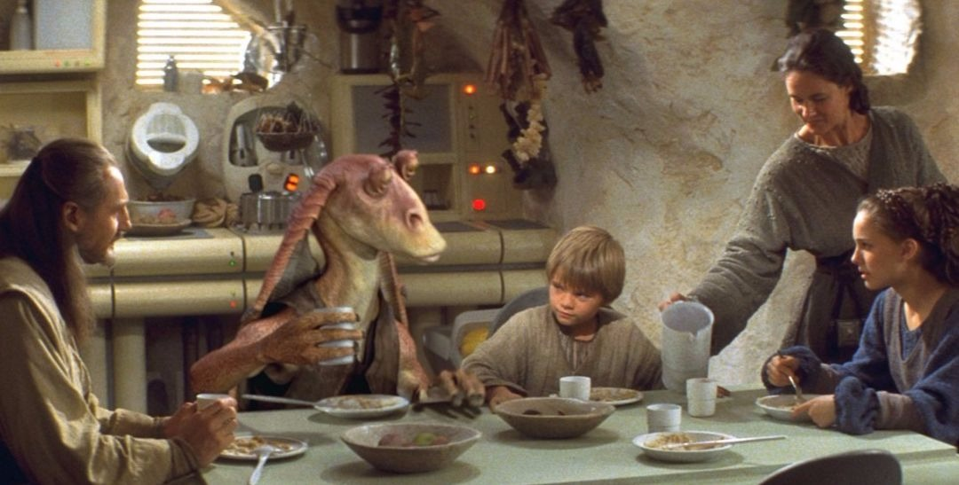 Young Anakanin Skywalker sits down to eat with Queen Amidala and Qui‑Gon Jinn, in Star Wars: Episode I – The Phantom Menace.