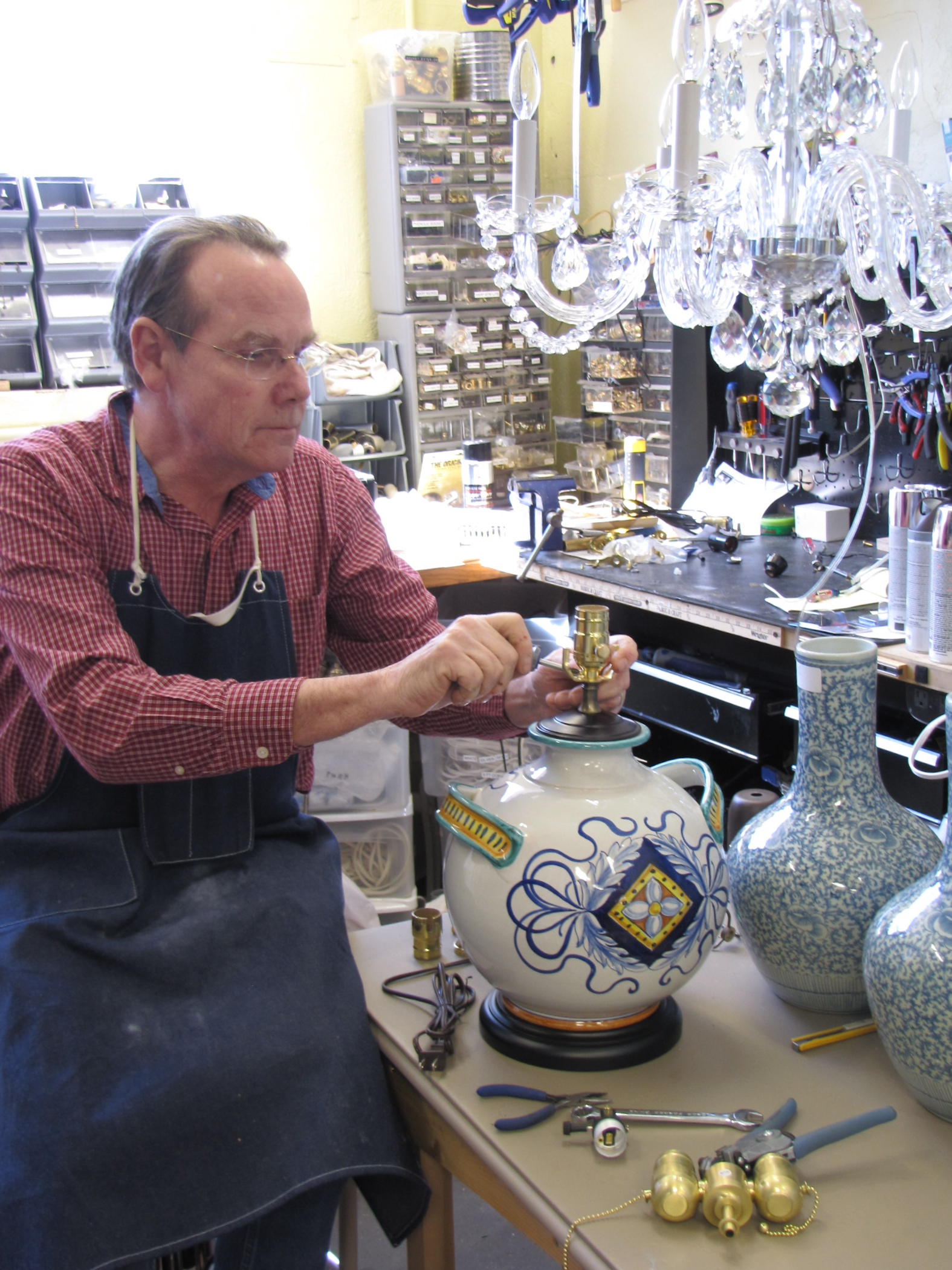 Mr. Holladay at his work bench making lamps from vases.