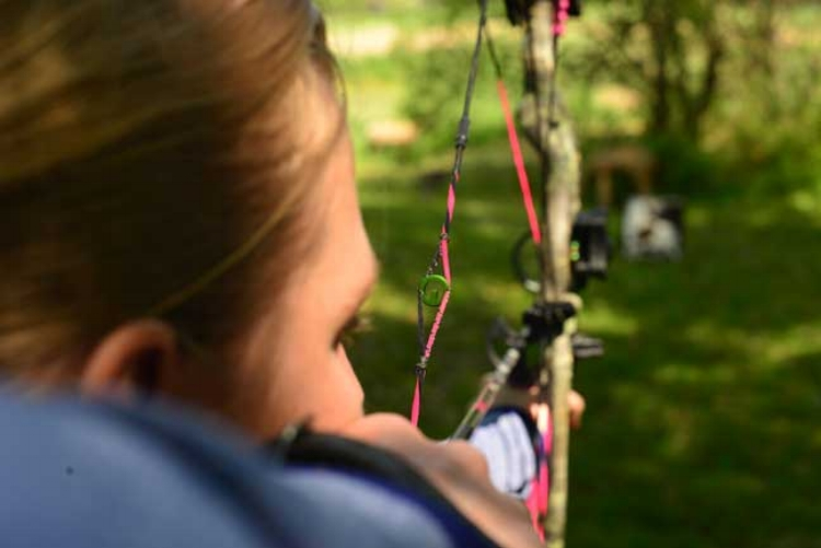 """Petersen's Bowhunting contributing writer Tony Peterson, has his wife try the Precision Peep sight. The caption reads, """"Peep sights have come a long way, with the latest, like the Precision Peep, not only offering a larger sight window, but also reinforcing proper shooting form."""""""