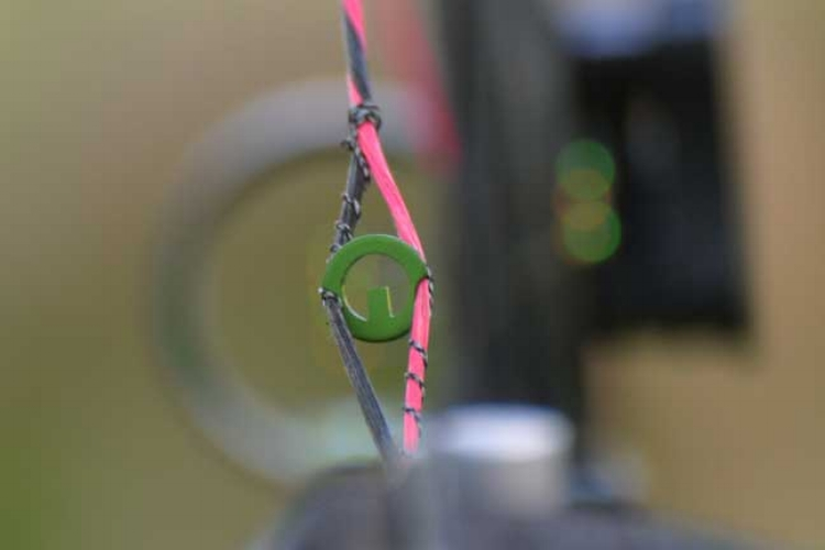 """Photo of a Precision Peep served into the bow for Petersen's Bowhunting Peep Sight Review. The caption reads: """"With a Precision Peep, you simply align the post with the correct pin so that you'll know your form is perfect""""."""