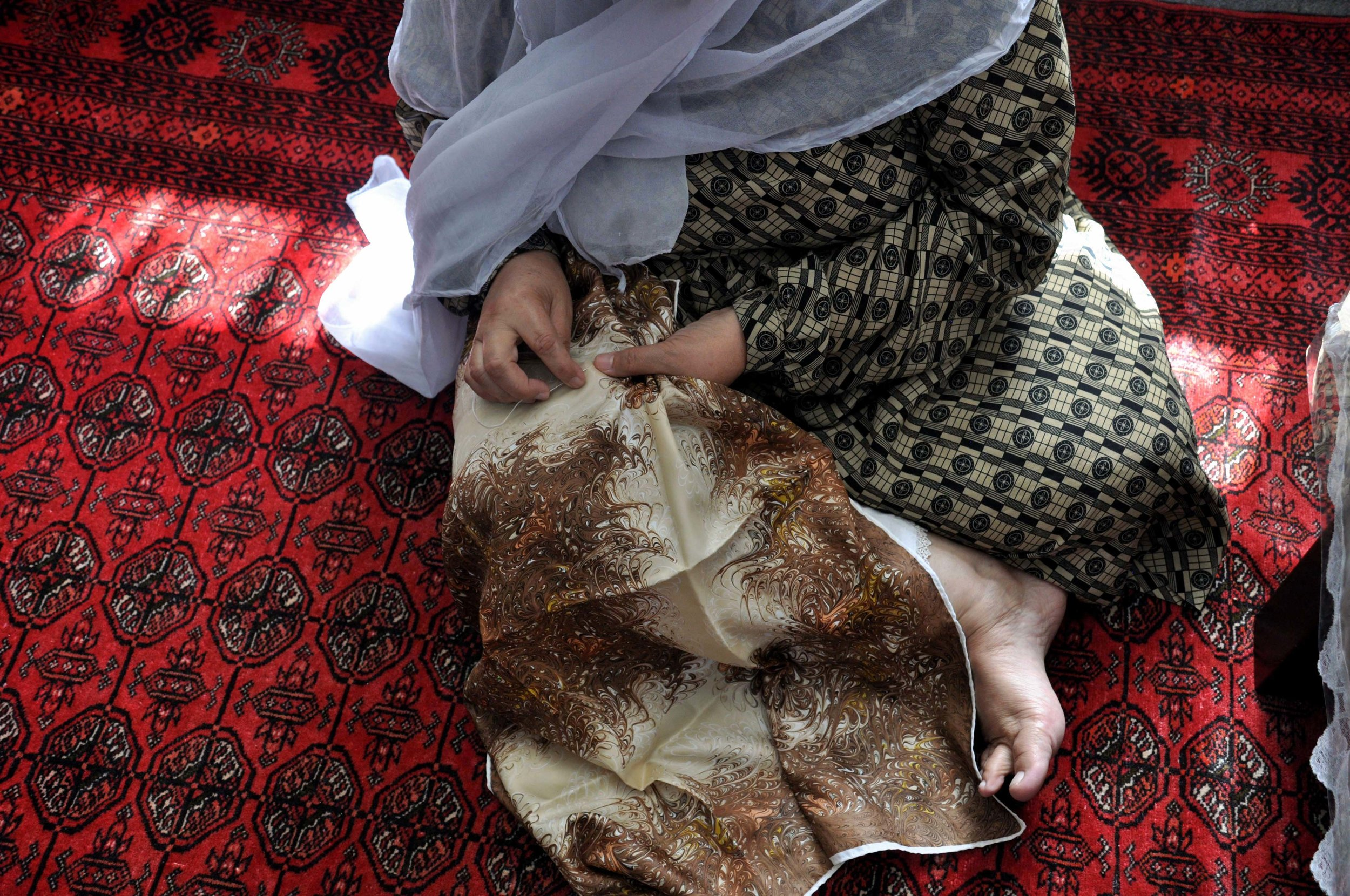 Hand embroidery of vintage silk scarves, refugee