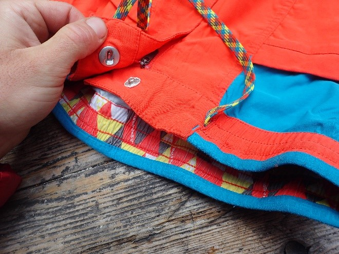 """Instead of snapping, the button slides into place like a good nut placement. I find this easier to do under a harness. The stretchy shoelace drawstring keeps the pants up with minimal bulk, and the waist band is wide, low profile, and lined on the top with a padded fuzzy material, making the pants supremely comfortable under a pack or harness. The Crimpers have all 4 of these design elements, as well. Fine design features typical of LaSpo like the inner waistband pattern and """"La Sportiva"""" inset on the waistband liner can be seen here."""