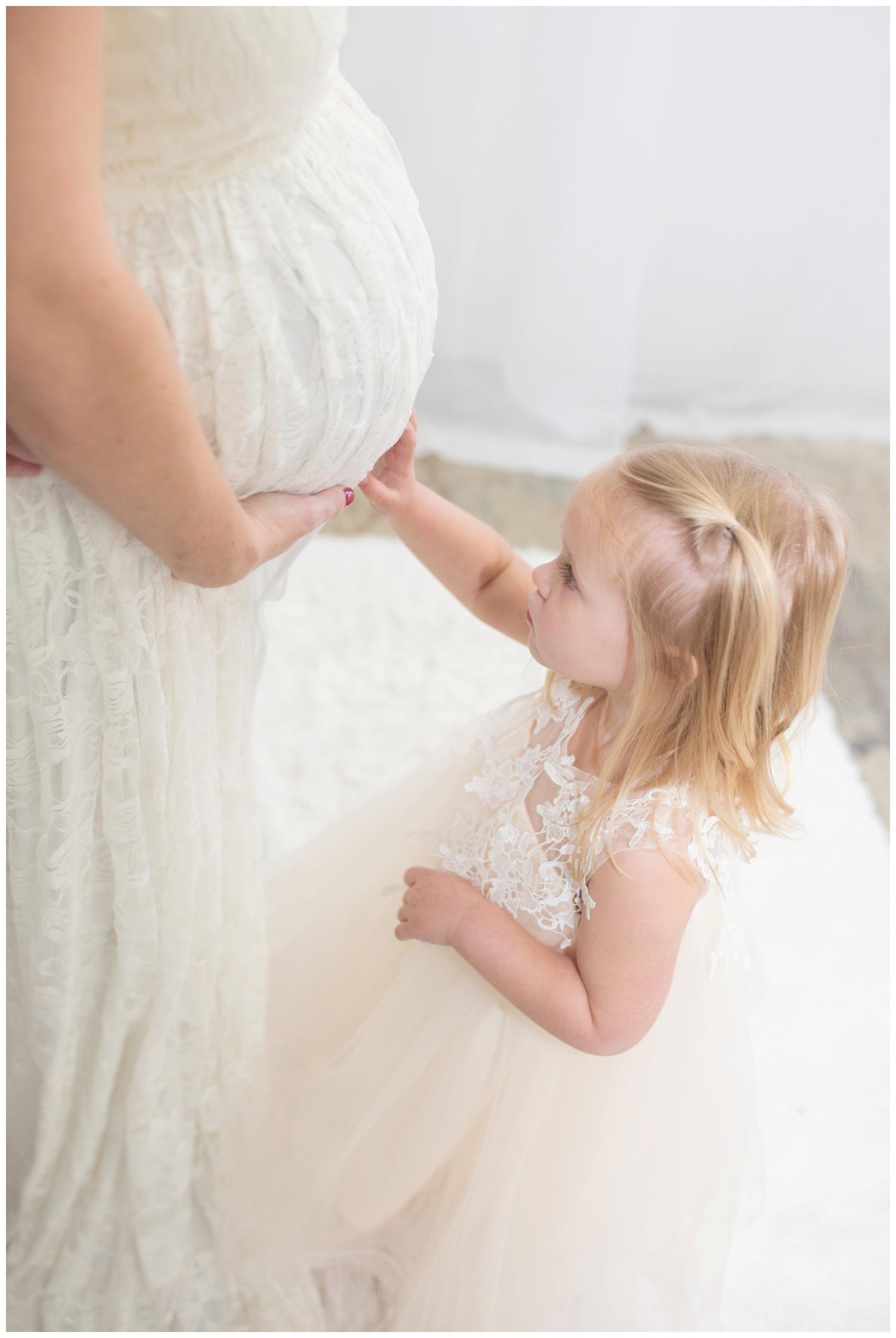 Reno maternity photographer girl touching moms belly kristi gayton photography