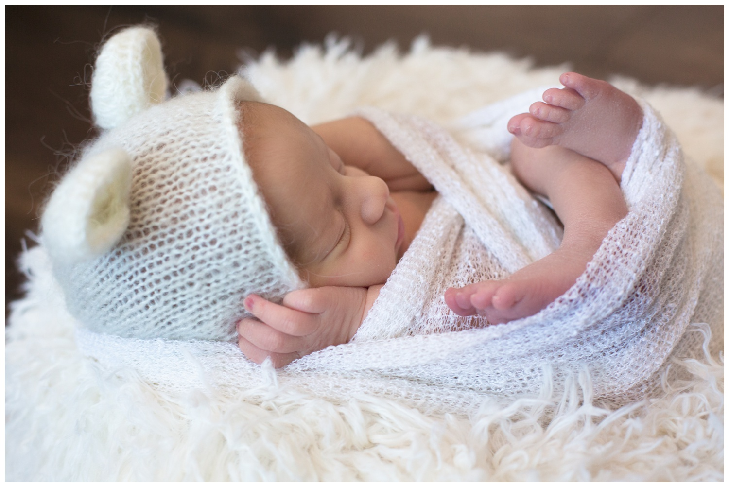 newborn pretzel wrap pose baby on back white teddy bear