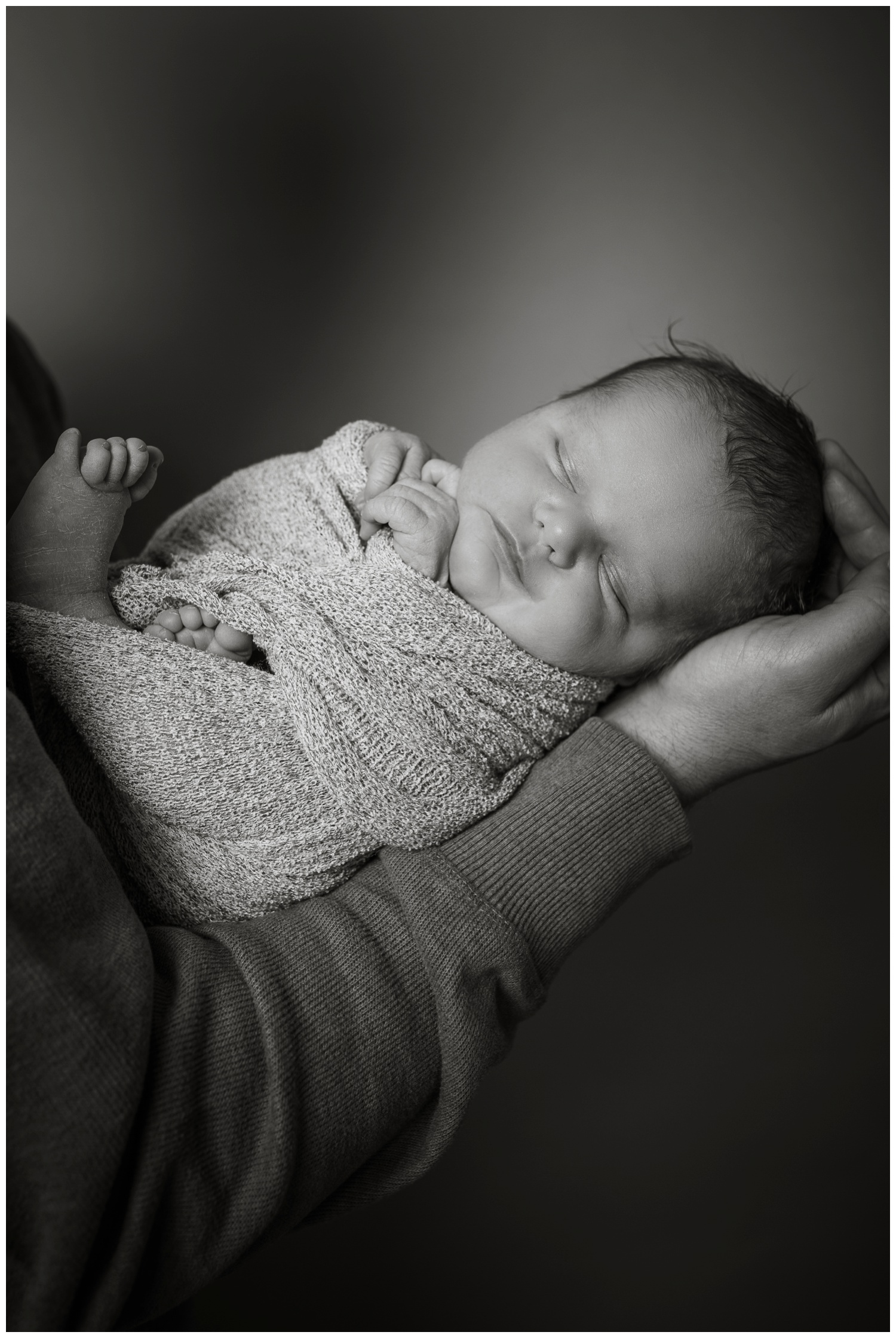 newborn Casey black and white in dads hands