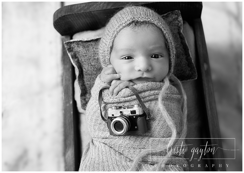 newborn with camera