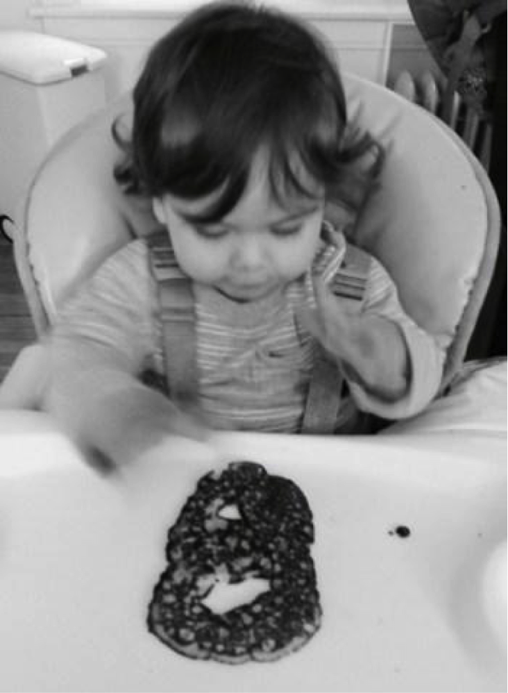 Excited toddler with their letter 'B' pancake!