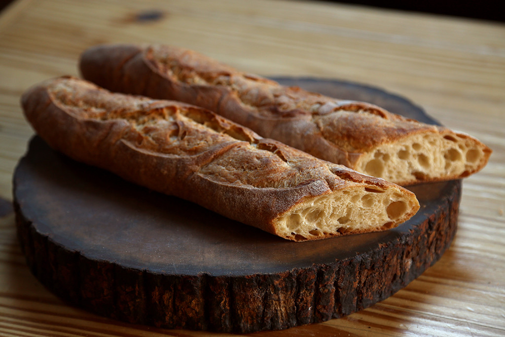 Baguette   Ours is a classic French Baguette, made from polish - which means it started the day before, a 24-hour process from mix to bake. This develops a rich flavor and a light, crispy crust. Hand-rolled, as each baker takes great pride in their own unique way of shaping them. Our baguettes are bathed in steam as they finish baking, which gives them their lovely sheen.