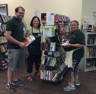 Volunteers Jeremy, Margaret and Teresa restock the Ongoing Sale shelves.