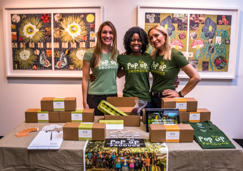 Vendor booth setup for Repurposed: Fashion Show + Auction. Shown (left to right): Pop Up Produce Founder, Amanda Zullo; Kit Owner and Volunteer, Demetria Cox; Kit Owner and Volunteer, Nina Zullo