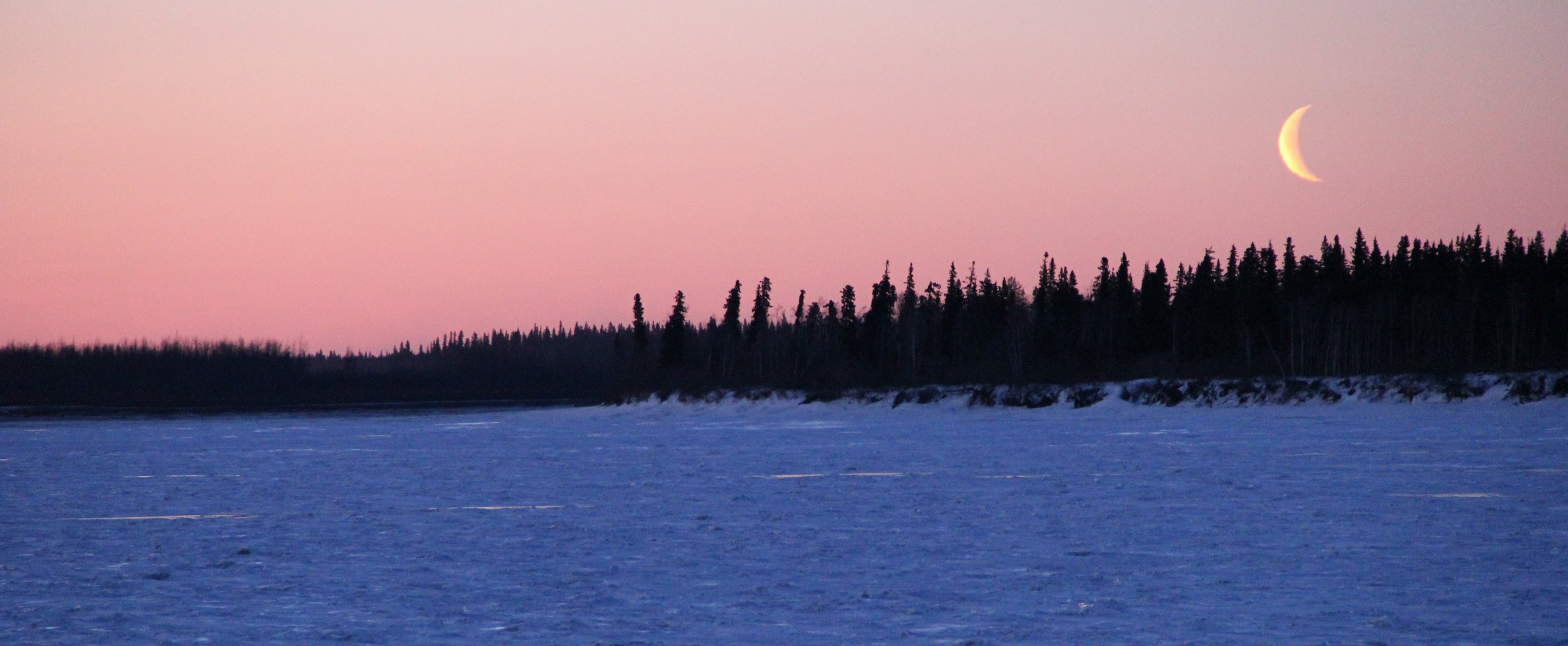 The moon going down on the far side of the Frozen Yukon