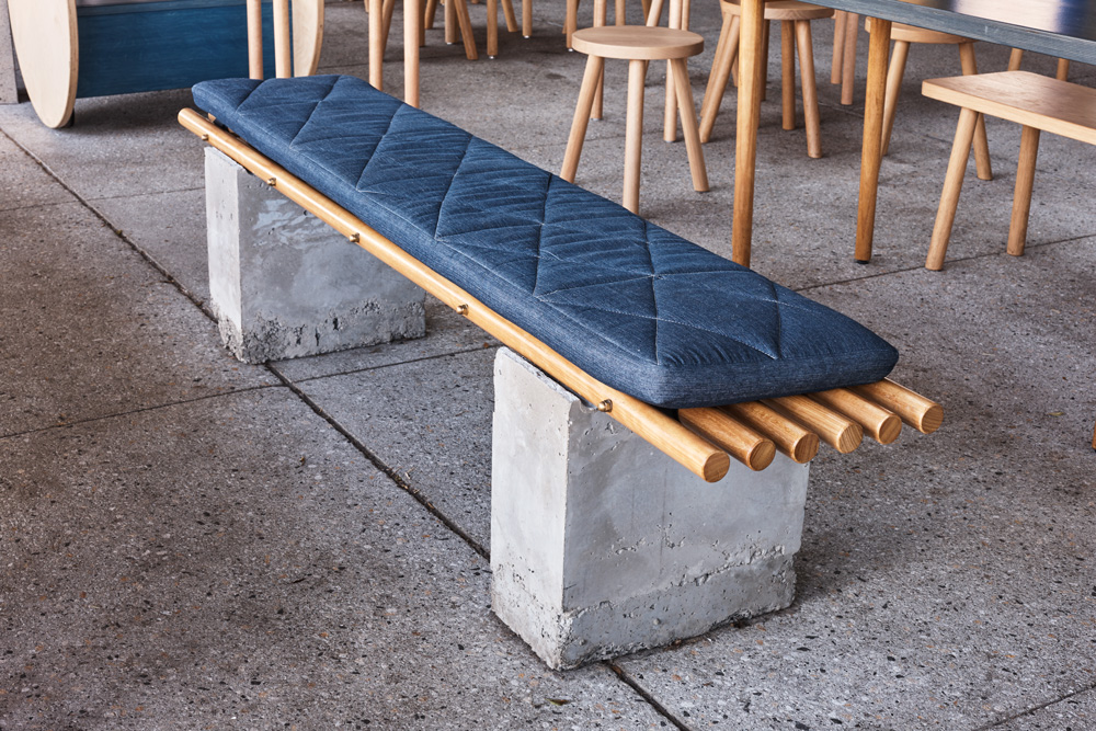 This bench comprised of pre cast concrete stumps. A series of timber dowels were nestled into grooves to the top of each of the bases. Denim seat pads with diamond cross stitching provided the perfect perch.
