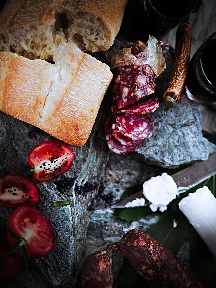 A TOAST 05 #truss #tomatoes #bread #focaccia #salami #glasses #red #wine #stone #slates #goats #milk #cheese #old #knife #bone #handle